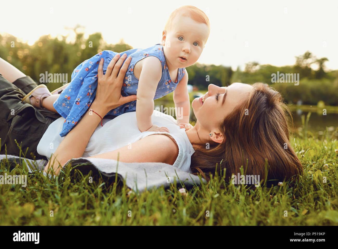 La madre e il bambino gioca su erba nel parco. Immagini Stock