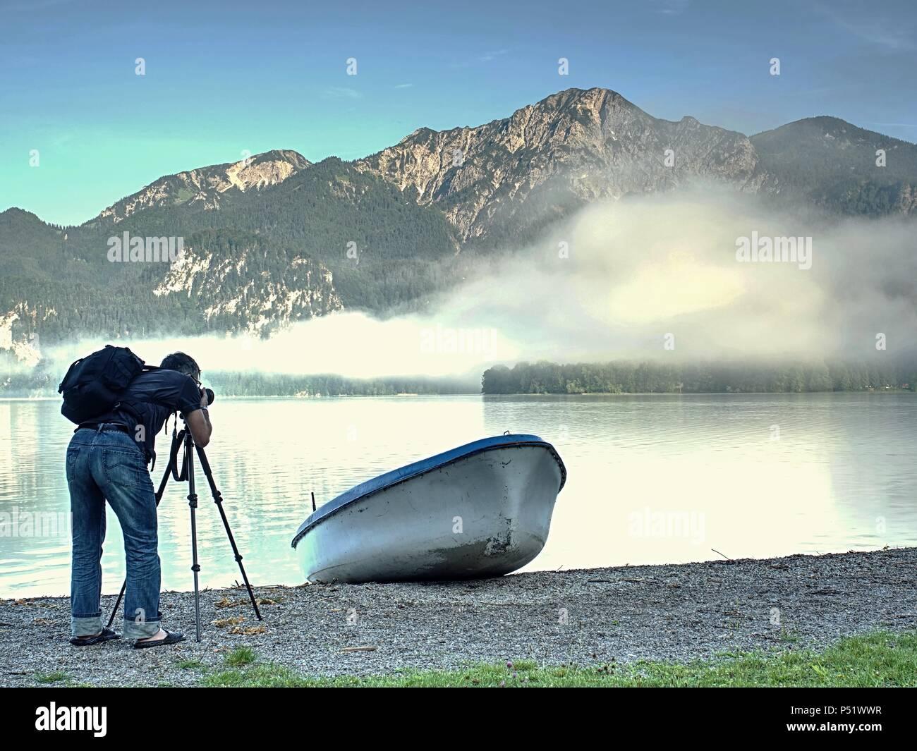 Fotografo con occhio al mirino è tenuto foto del lago con le montagne delle Alpi in background. Opere dell'artista. Immagini Stock