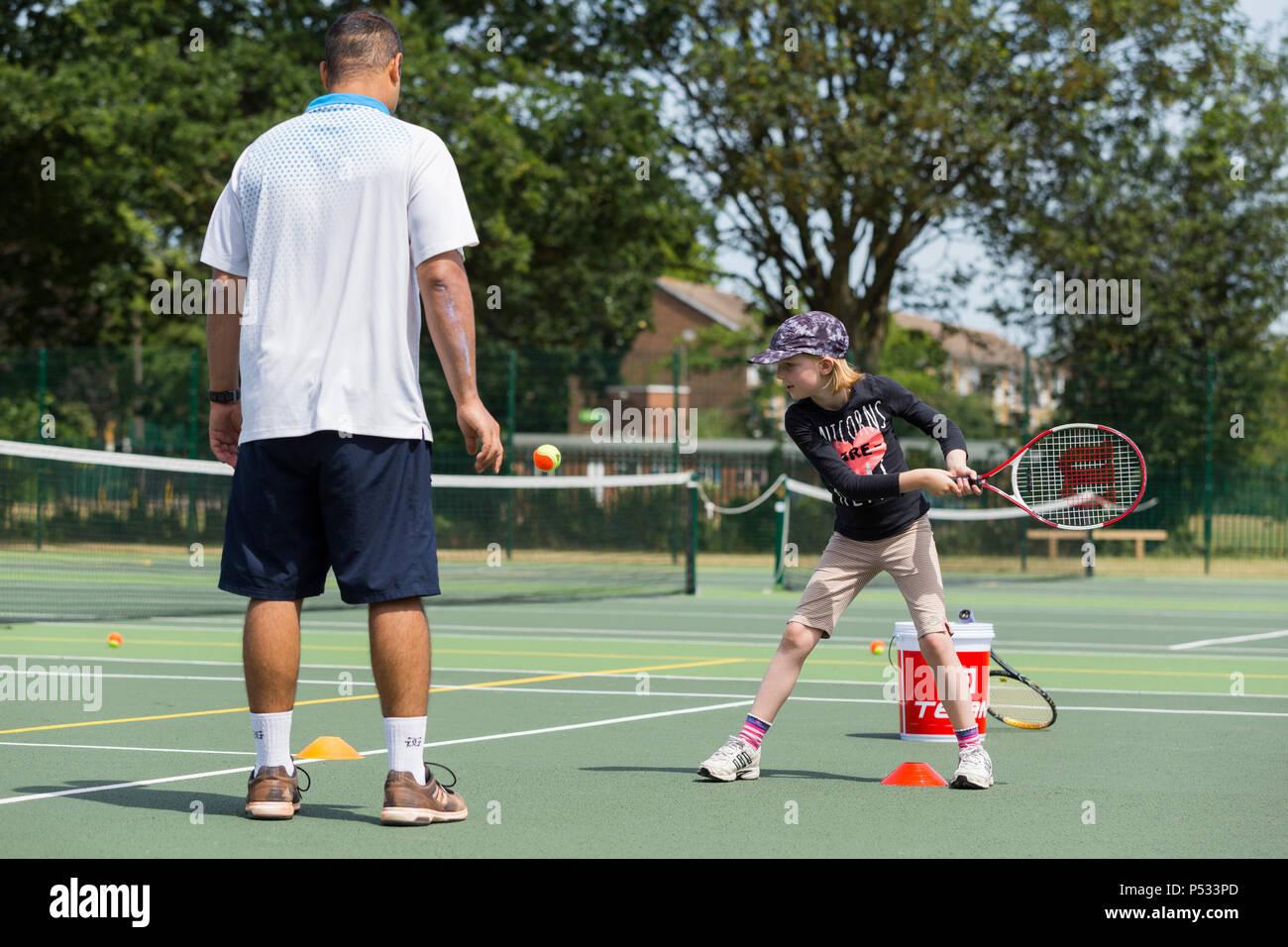 Tennis per bambini la sessione di coaching / lezione che si svolge su una full-size campo da tennis con i bambini / bambini e professional tennis pullman, in estate. Regno Unito. (99) Immagini Stock