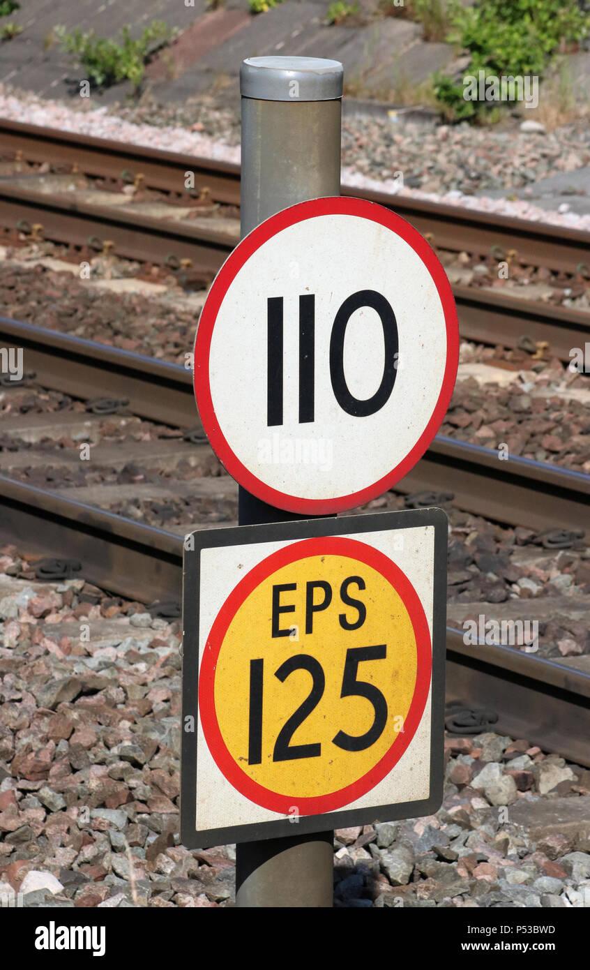Limite di velocità (110) e maggiore velocità consentita (EPS 125) segni a lato del binario ferroviario sulla linea principale della Costa Occidentale (WCML) a Carnforth, Lancashire, Regno Unito. Immagini Stock