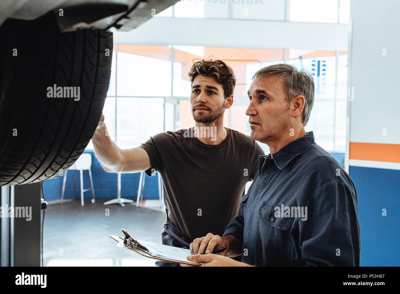 Il meccanico che mostra la ruota di auto al collega rendendo note in Appunti. Auto professionisti del servizio esaminando la vettura e rendendo note. Immagini Stock