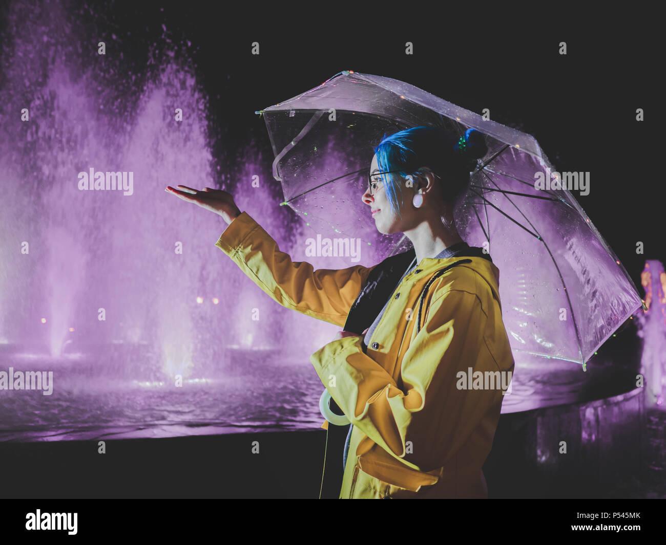 Giovane ragazza carina con blu capelli tinti in giallo impermeabile