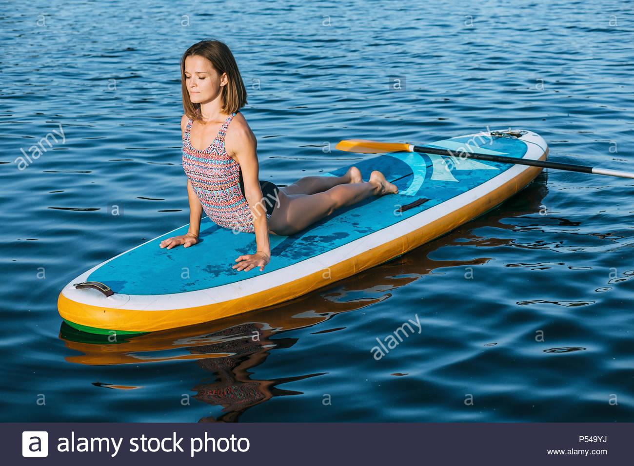 La donna a praticare yoga su paddleboard Immagini Stock