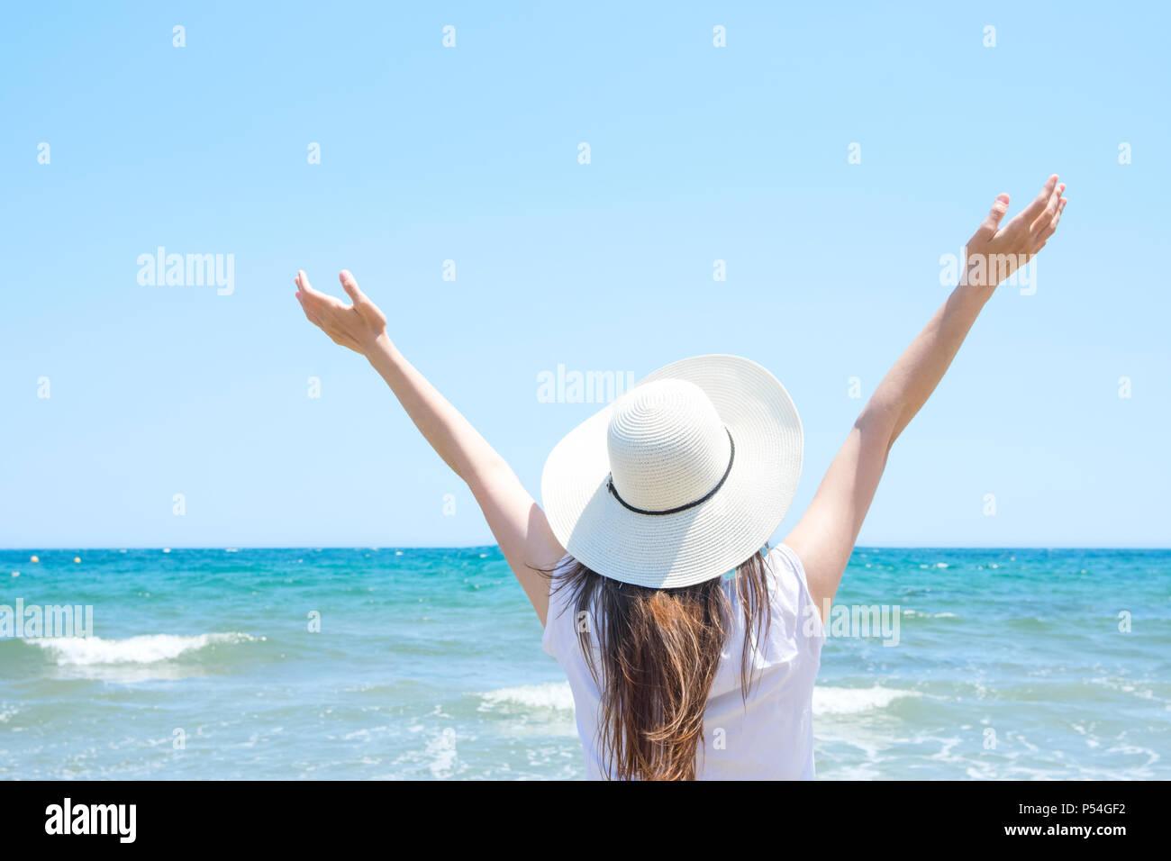 Piuttosto giovane donna caucasica con lunghi capelli castani in Hat mani sollevate in aria si erge a Beach guarda al mare turchese orizzonte sul cielo blu indietro Immagini Stock
