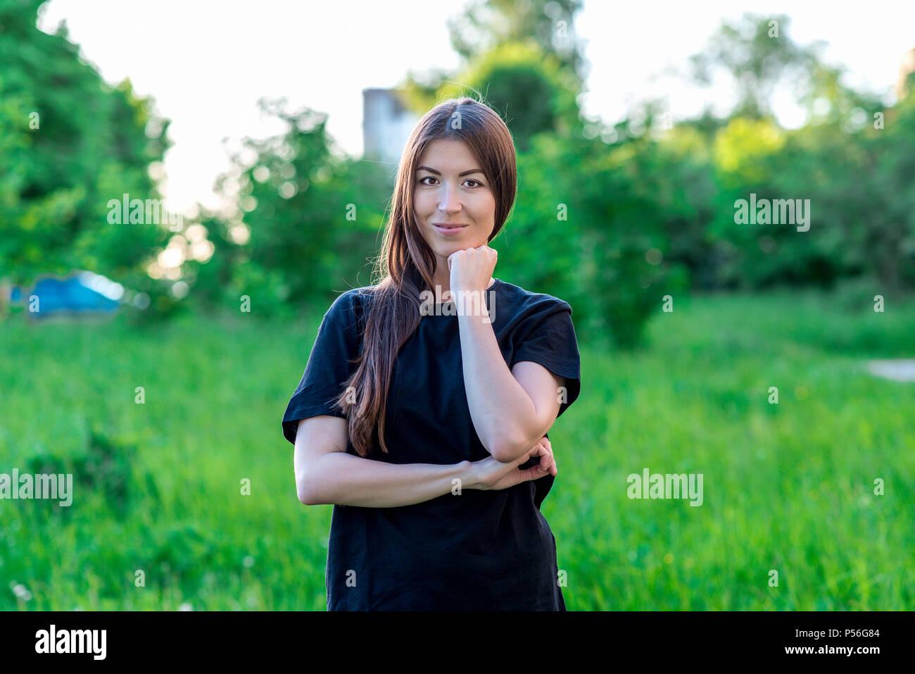In estate nel parco all aria fresca Lieti sorrisi. Tiene per mano con la sua  mano. Capelli lunghi. In una black T-shirt abiti di tutti i giorni tra i ... 50d08516e41