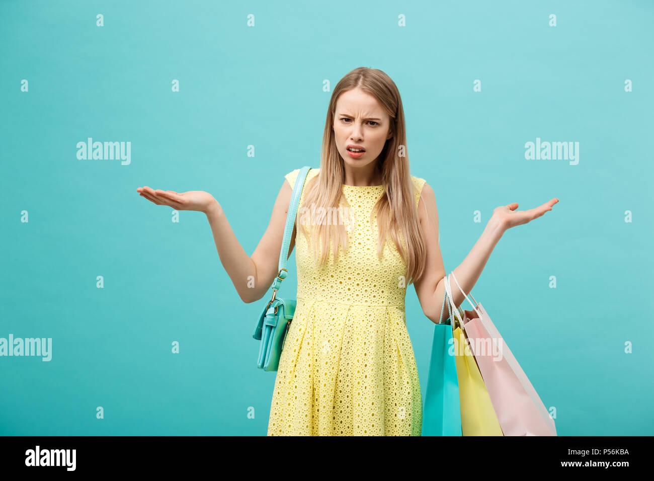 Shoping e concetto di vendita: bella infelice giovane donna in giallo abito elegante con shopping bag. Immagini Stock
