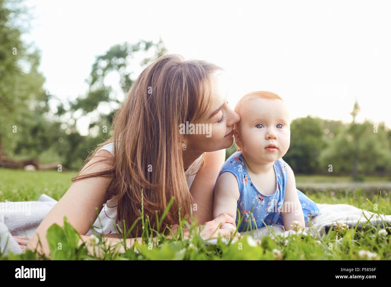 La madre e il bambino gioca su erba in estate park Immagini Stock