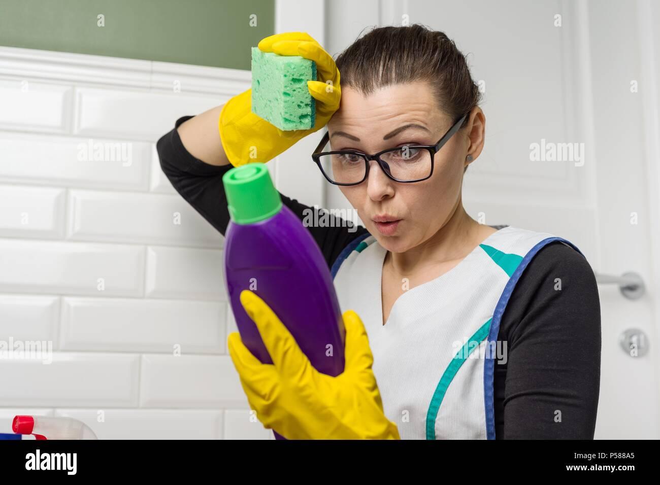 Donna casalinga fa la pulizia con lettura di interesse le istruzioni sul detersivo. Immagini Stock
