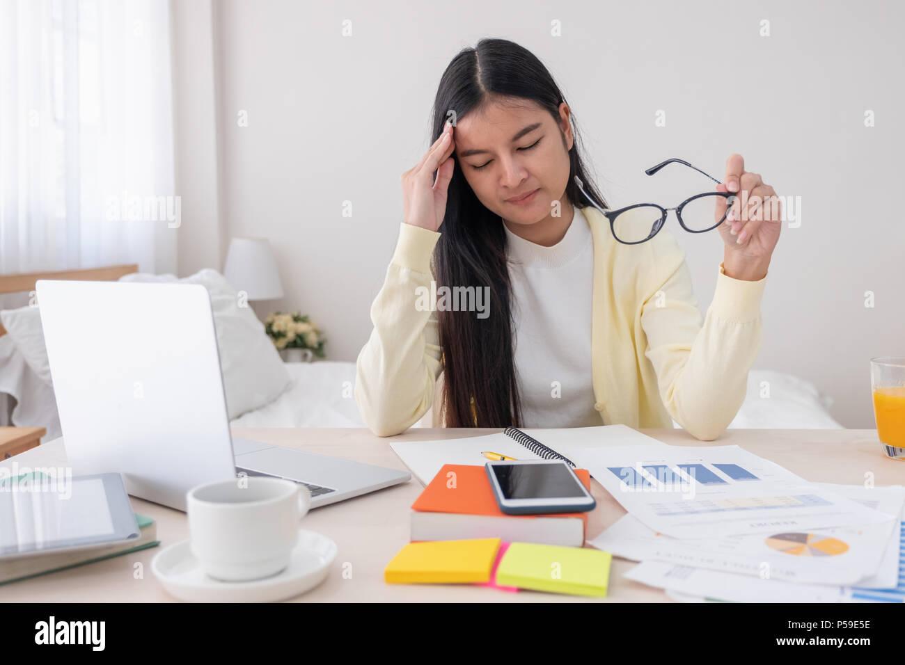 Femmina asiatica freelancer mal di testa e stress mentre si lavora con il computer portatile sul tavolo in camera da letto a casa.Il lavoro a casa concetto.lavorare da casa concept Immagini Stock