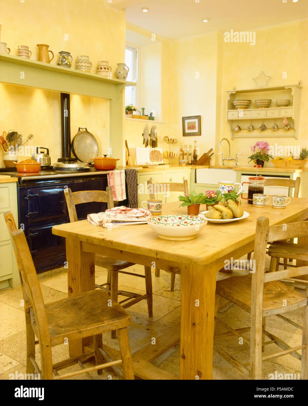 Sedie di pino e pesante tavolo di pino giallo in cucina di paese con ...