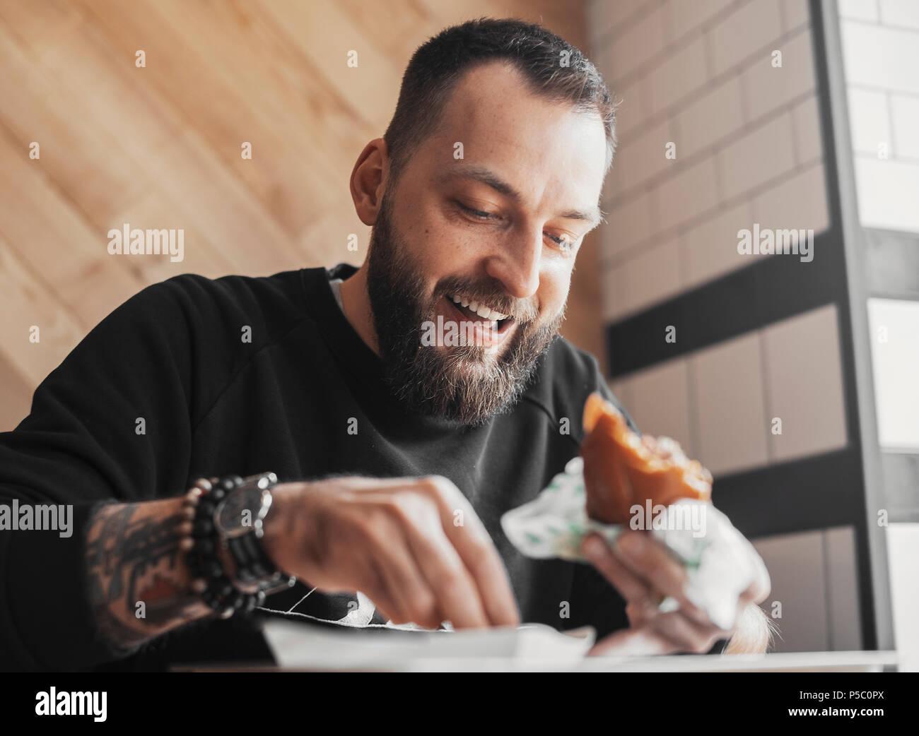 Giovane uomo barbuto mangiare hamburger e sorridendo vicino. Immagini Stock