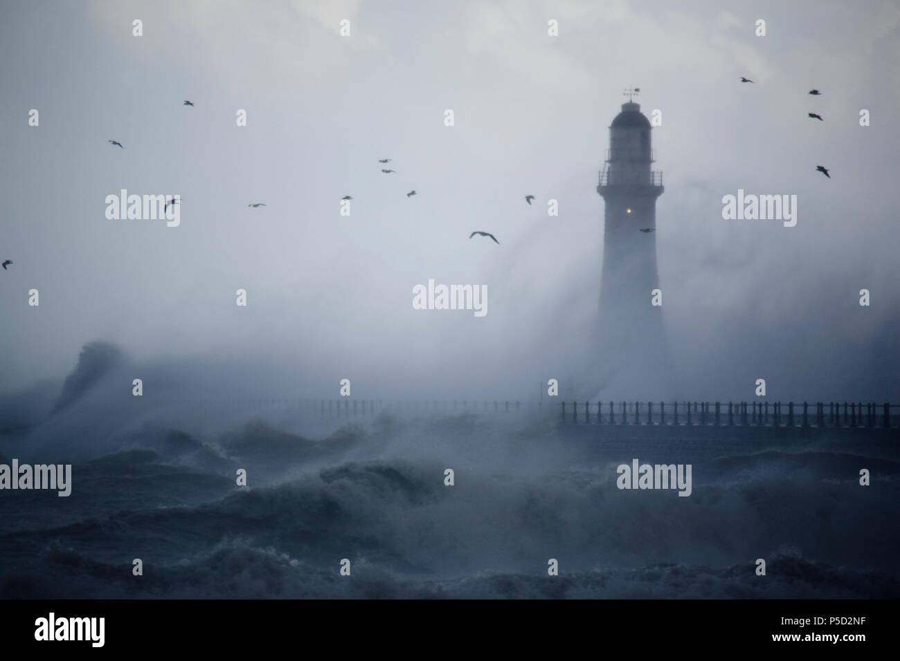 Venti violenti e le onde battono Roker Pier, Sunderland durante un est che gale combinato con alte maree Immagini Stock