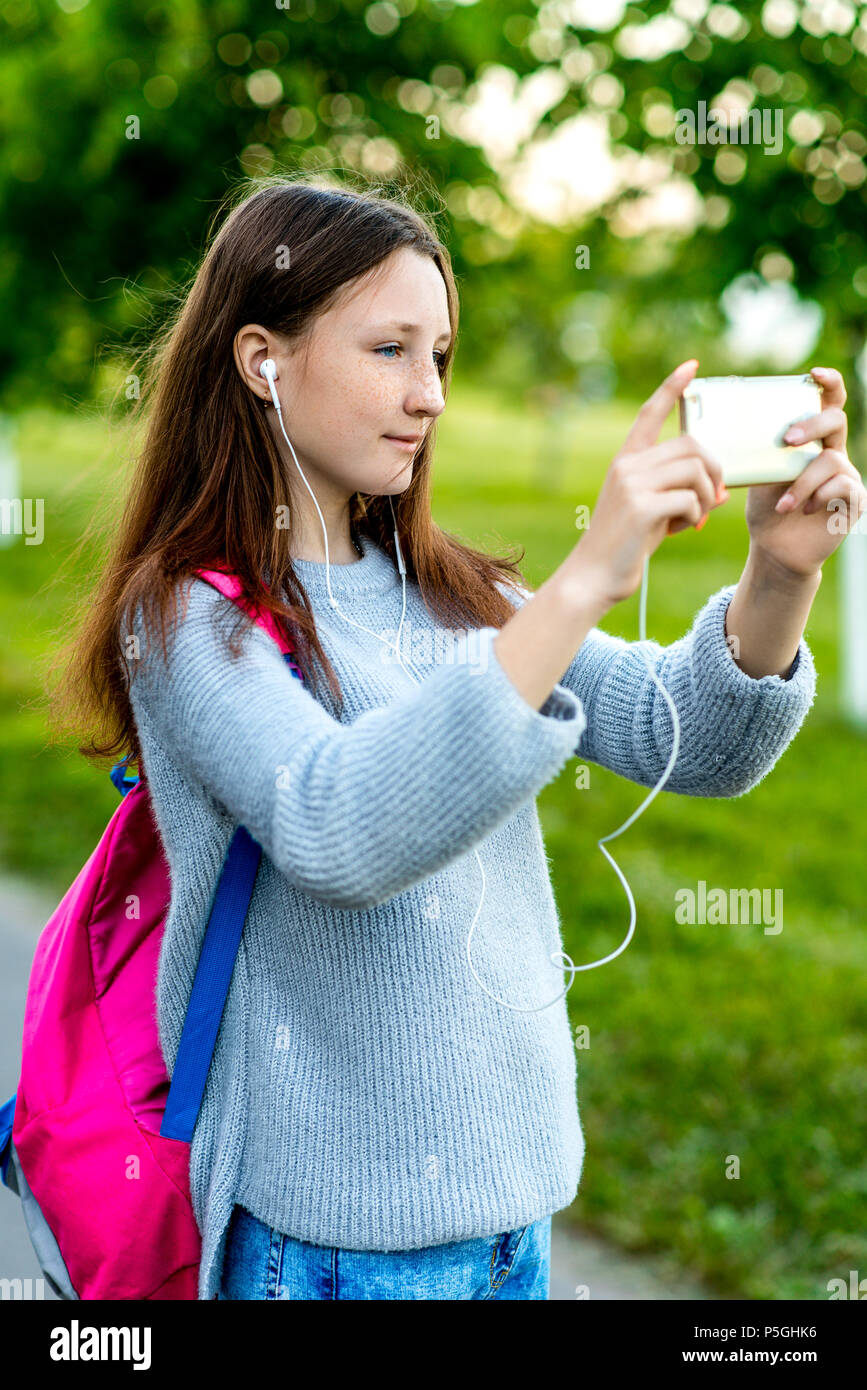 Bella schoolgirl ragazza adolescente. In estate la natura. Nelle sue mani  detiene uno smartphone dietro il suo zaino. Fotografie sul telefono. 9e786123ff17