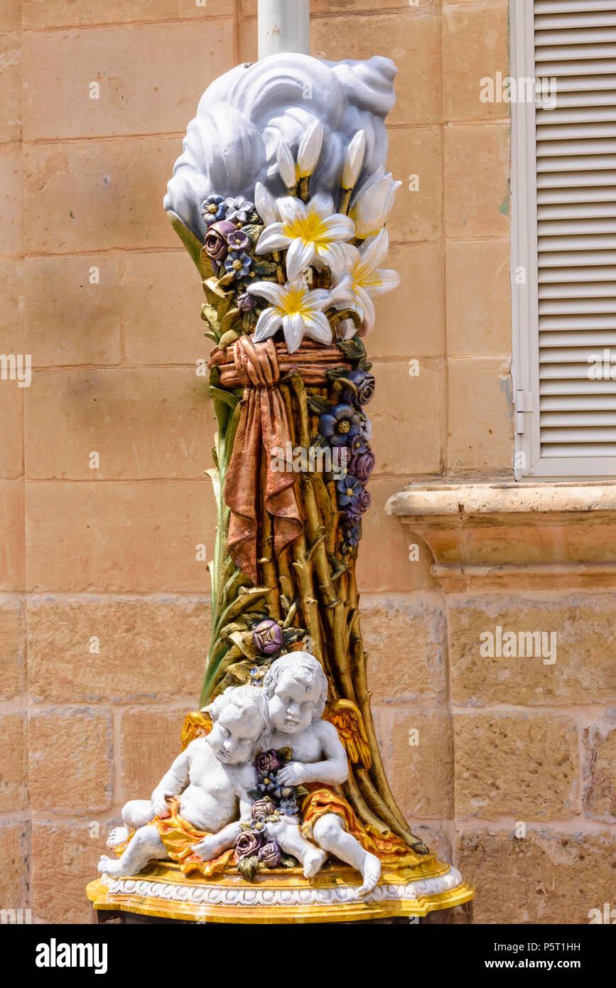 Una decorazione in fibra di vetro è attaccato ad un lampione in anticipo di una cerimonia religiosa di Nadur, Gozo, Malta Immagini Stock