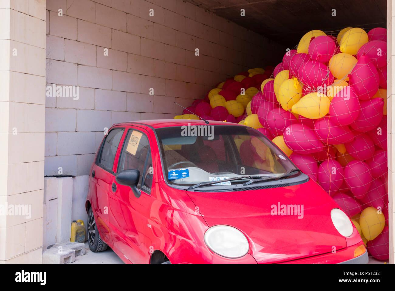 Rosso e giallo palloncini intrappolato in un garage di un'auto in anticipo di una festa religiosa, Xwekija, Gozo, Malta Immagini Stock