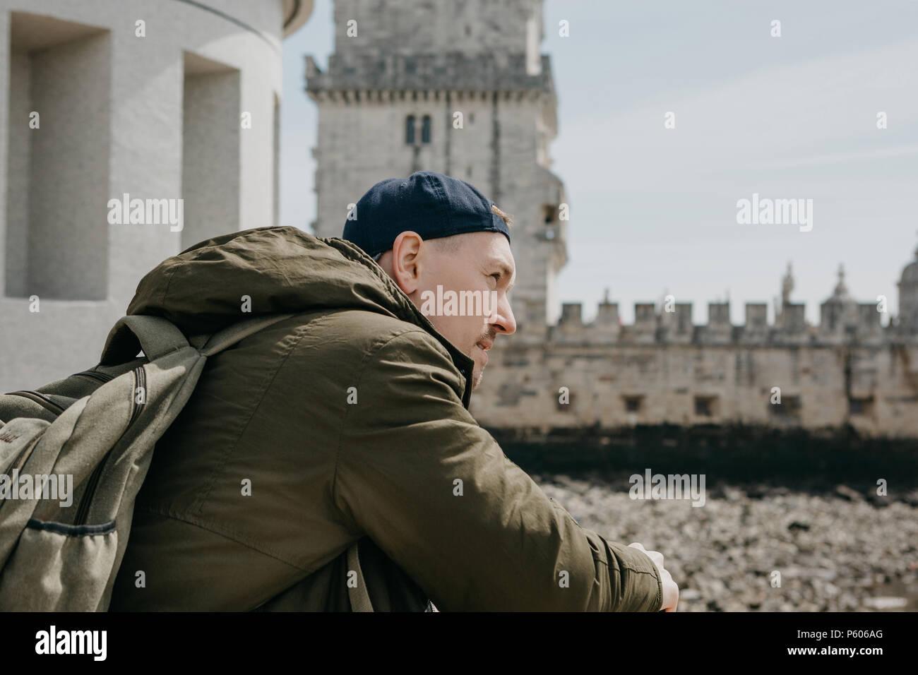 Ritratto di un giovane turista ragazzo o uomo di viaggiatori con lo zaino che si siede e guarda nella distanza di Lisbona in Portogallo. La Torre di Belem in background Immagini Stock
