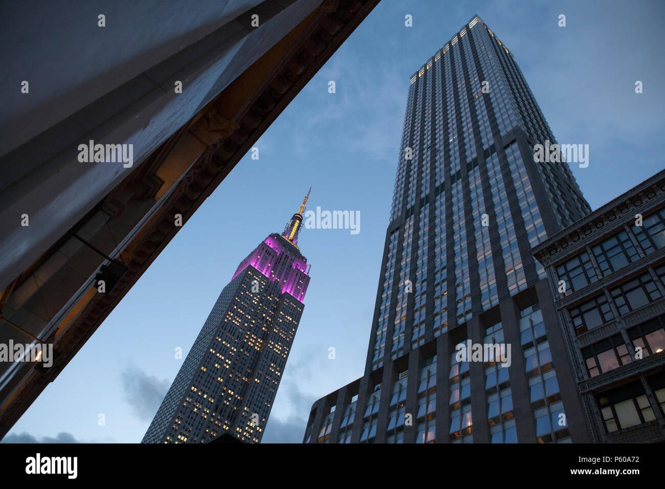 La art-deco architettura di New York Empire State Building raggiunge il cielo al tramonto Immagini Stock