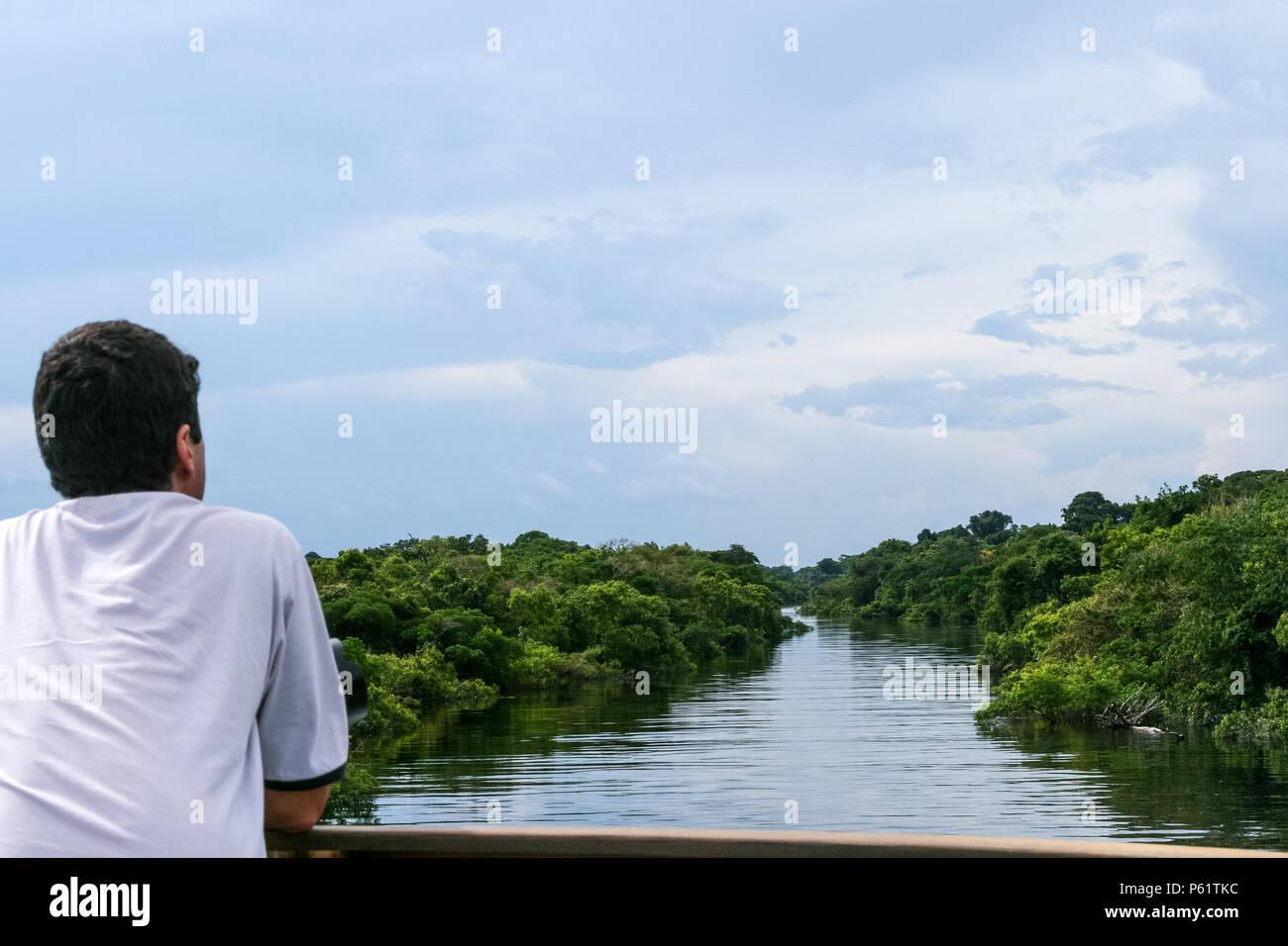 Amazonas, Brasile. Un turista contemplando la splendida vista del fiume Rio Negro durante la piena stagione con la foresta pluviale amazzonica in background. Foto Stock