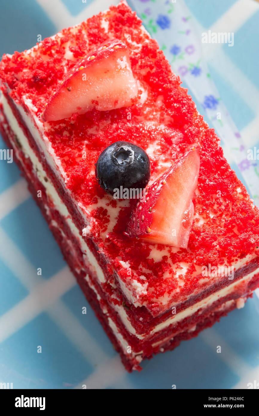 Torta rossa del velluto con crema e fragole e mirtillo Immagini Stock