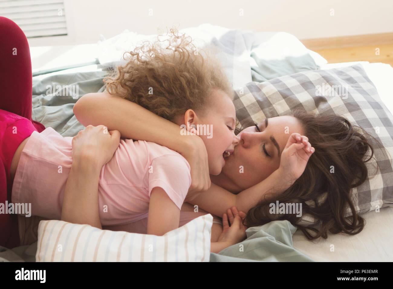 Mattina in famiglia. Madre baci e abbracci la figlia con capelli ...