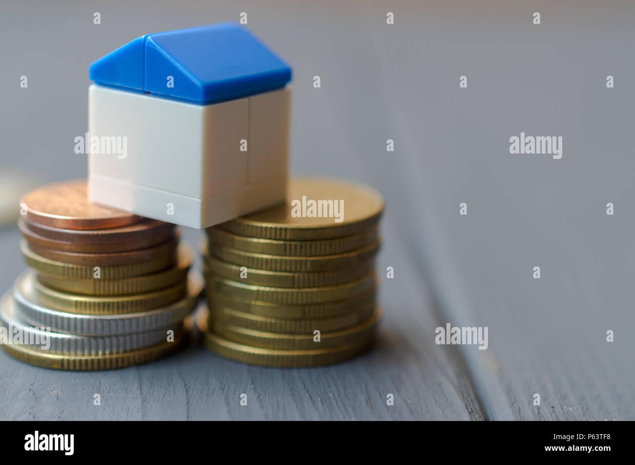 Il concetto di prestiti per l'alloggiamento. Casa bianca con un tetto blu su una pila di monete Foto Stock