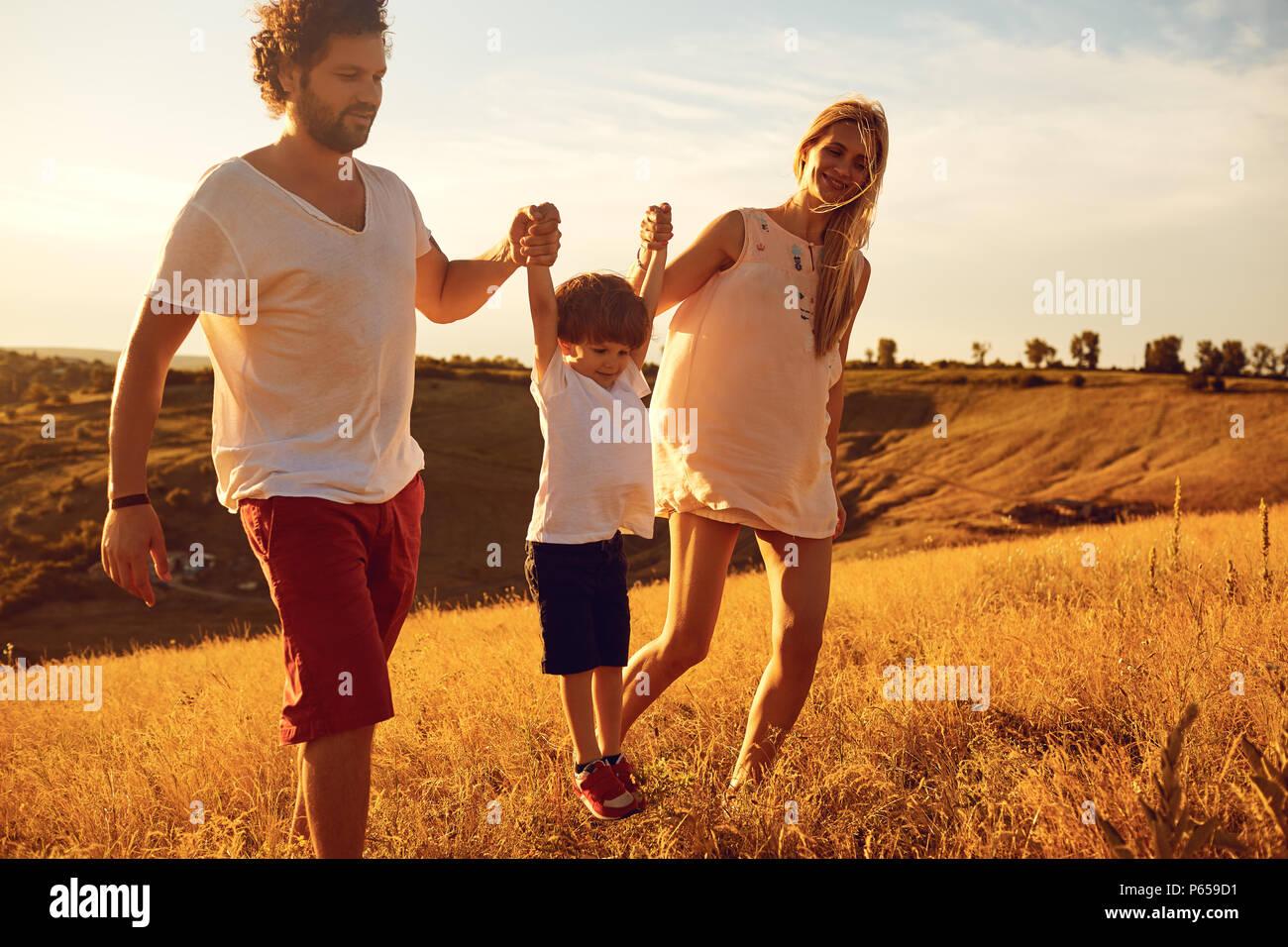 La famiglia felice divertirsi giocando al tramonto. Immagini Stock