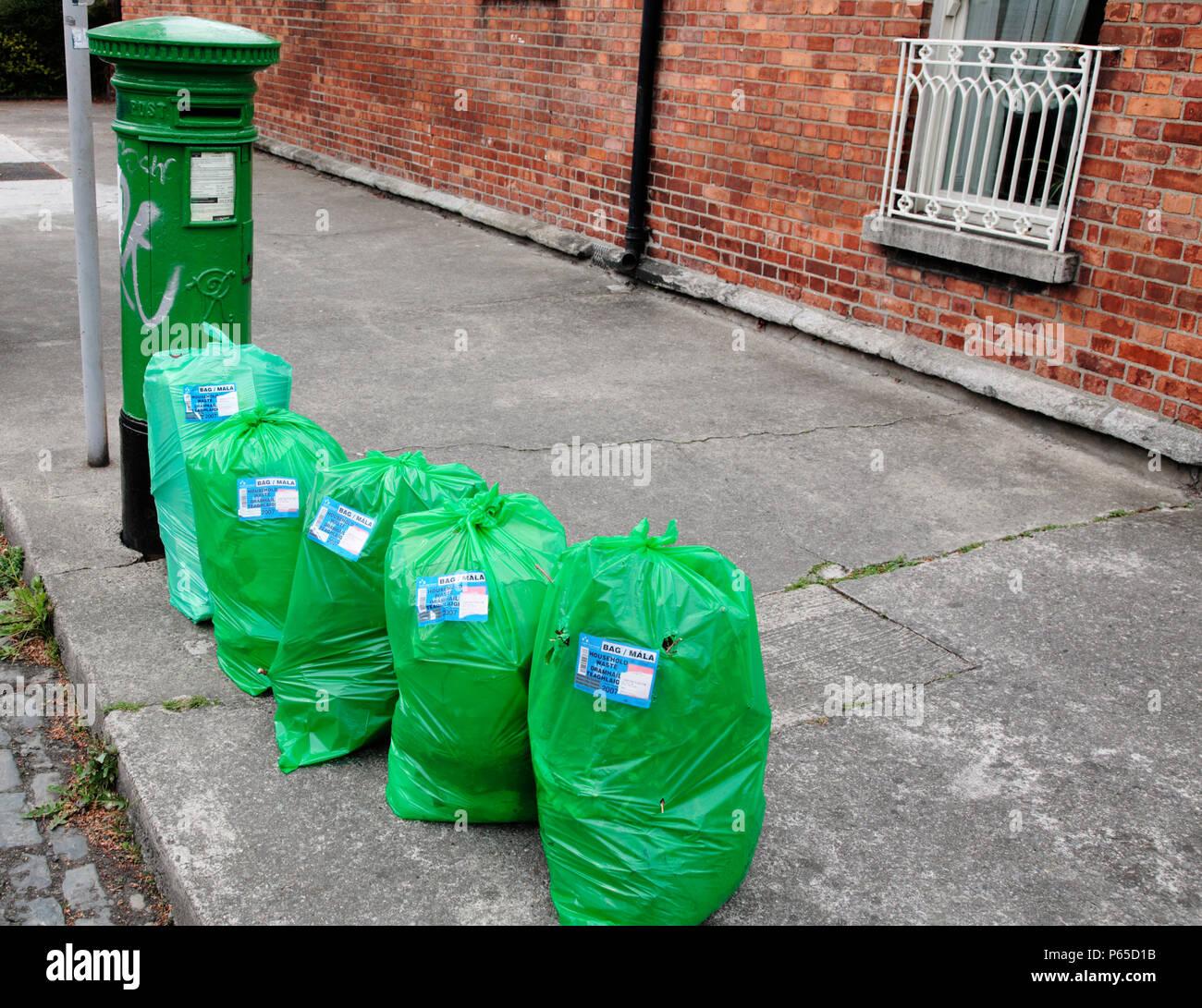 Sacchi per i rifiuti in attesa di raccolta, Dublino, Irlanda. La raccolta dei rifiuti è pagato con i tag che si acquista in anticipo e allegare al vassoio o rifiutare sa Immagini Stock