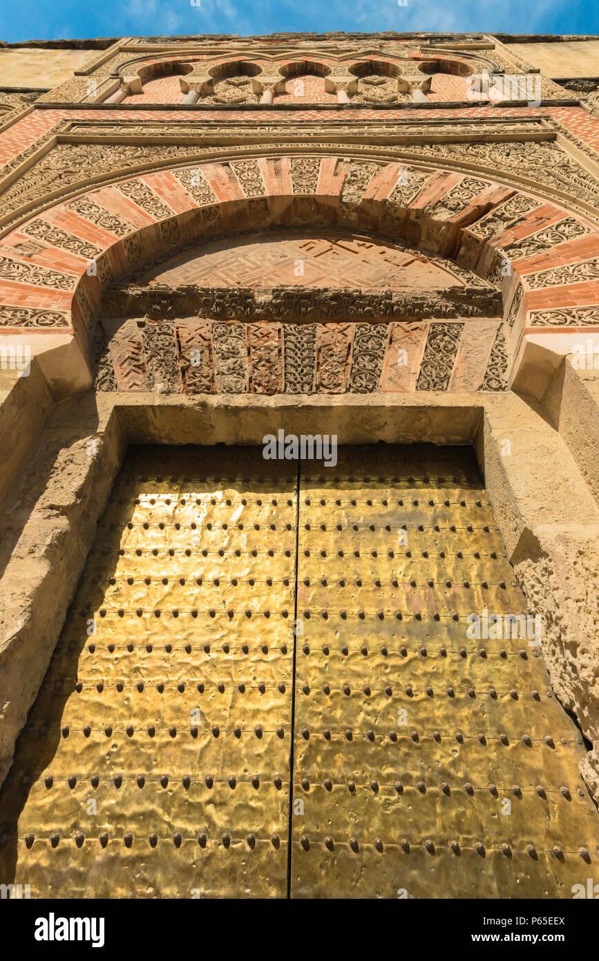 Spagna moresca, islamica vista di un enorme rivestito in ottone porta impostata entro un decorate in stile moresco ingresso alla Cattedrale Mezquita Moschea-complesso di Cordoba. Immagini Stock