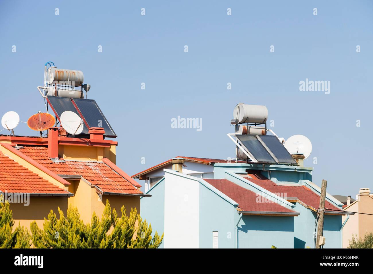 Caloriferi di acqua solari sui tetti delle case in Teos, Turchia. Immagini Stock