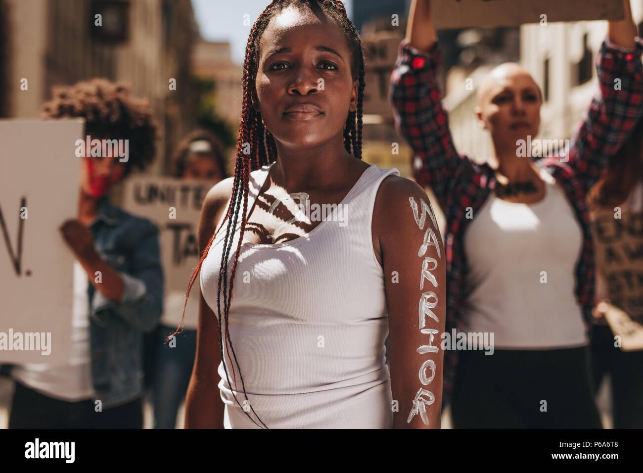 Giovane donna in piedi all'aperto con un gruppo di manifestanti sul retro. Donna con la parola scritta del guerriero sul suo braccio. Immagini Stock