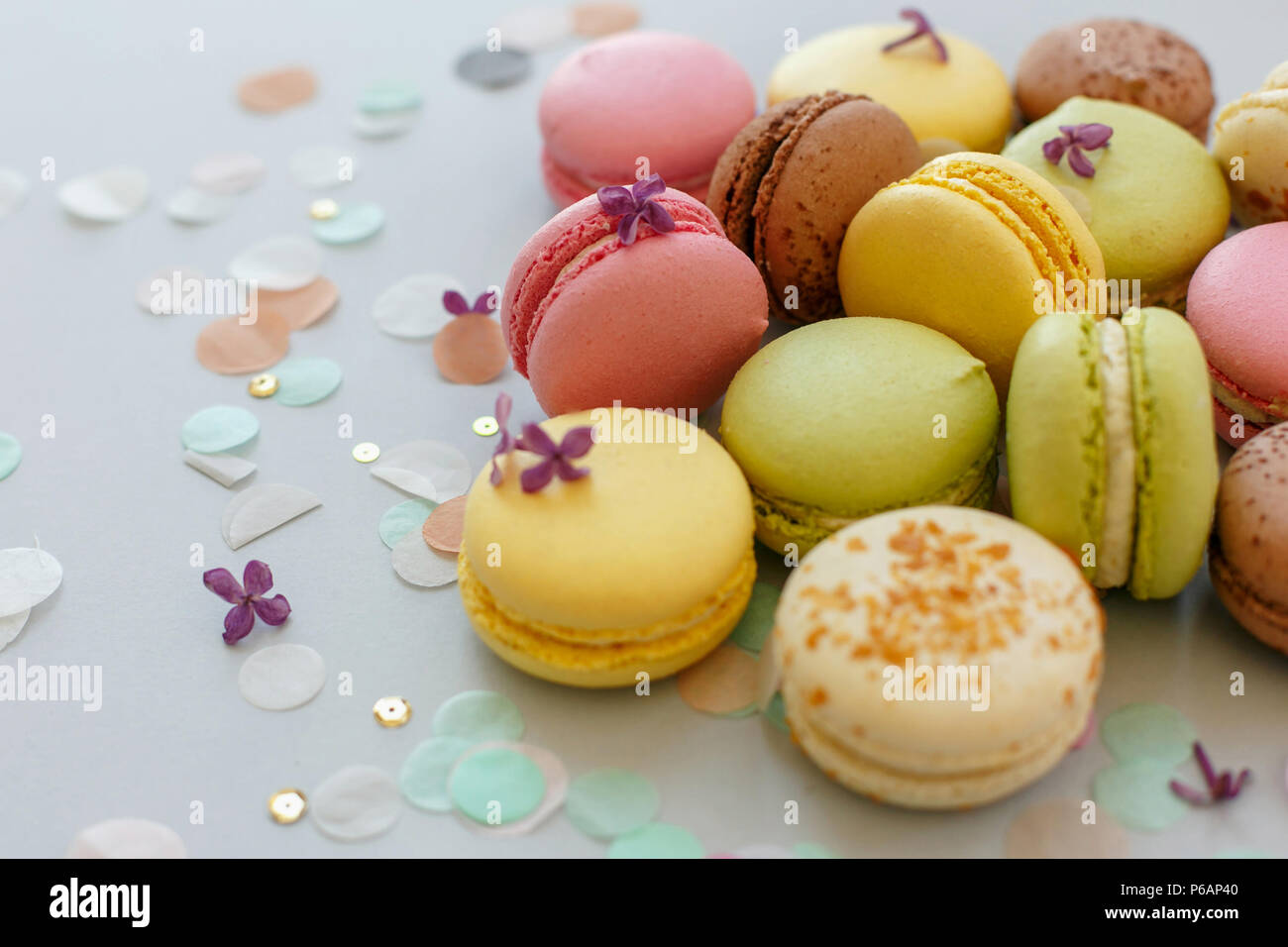 Macaron colorati sul trendy grigio pastello carta con fiori lilla e coriandoli. Gustose rosa, giallo, verde e marrone e amaretti. candy bar per party. foo Immagini Stock