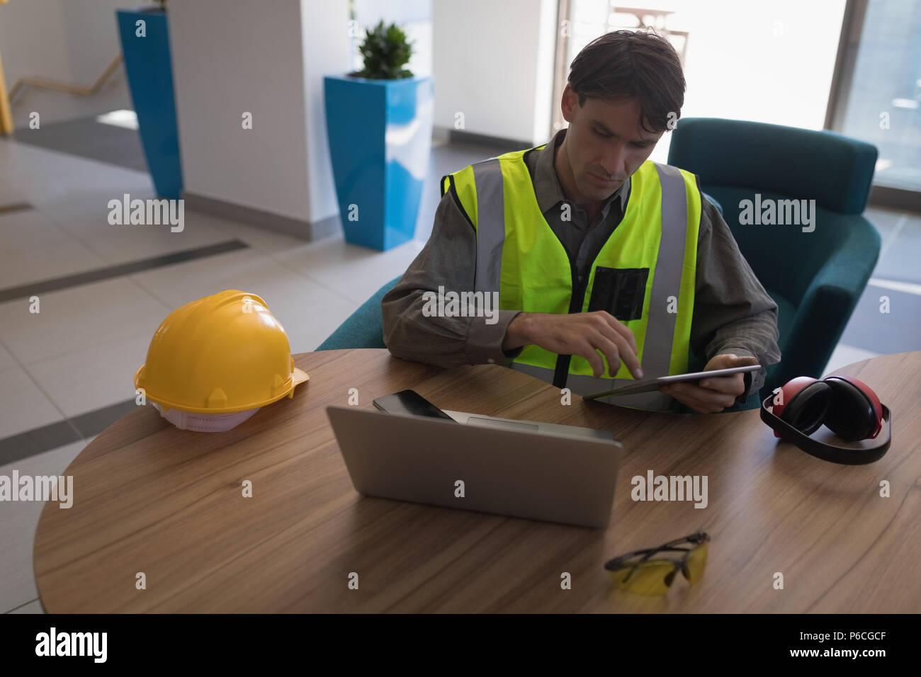 Lavoratore di sesso maschile con tavoletta digitale alla scrivania Foto Stock