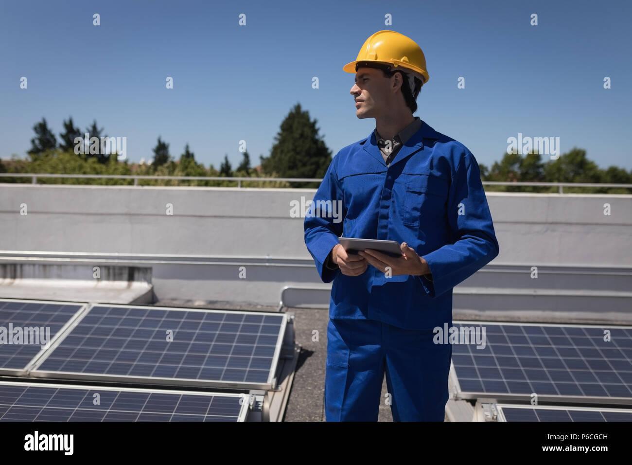 Lavoratore di sesso maschile con tavoletta digitale alla stazione solare Foto Stock