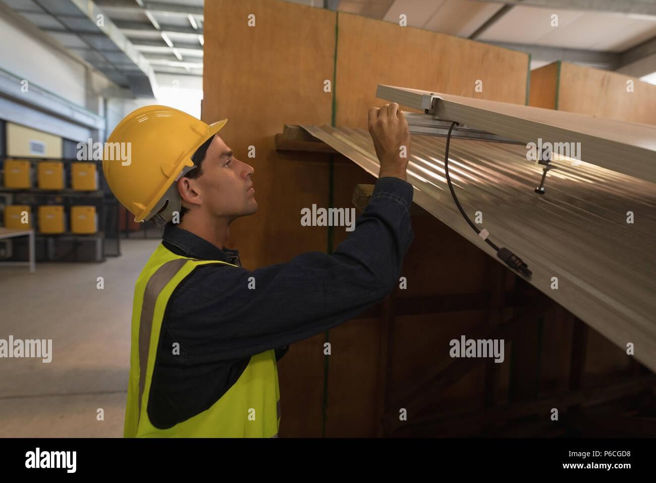 Lavoratore di sesso maschile lavora su pannello solare Immagini Stock