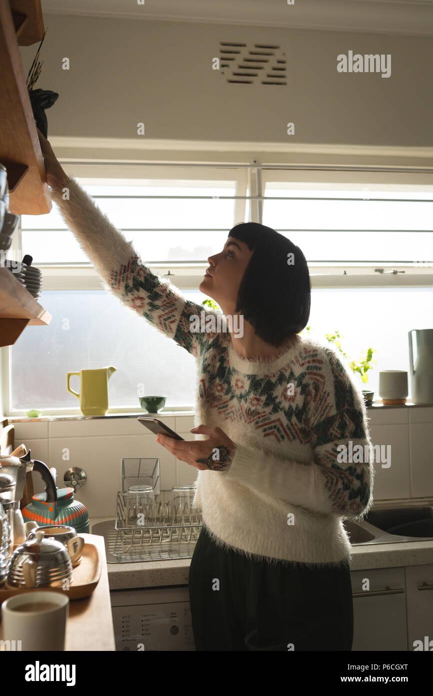 Donna che utilizza il telefono cellulare mentre si lavora in cucina Foto Stock