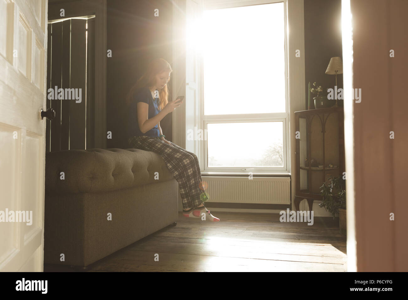 Donna che utilizza un cellulare in salotto Foto Stock