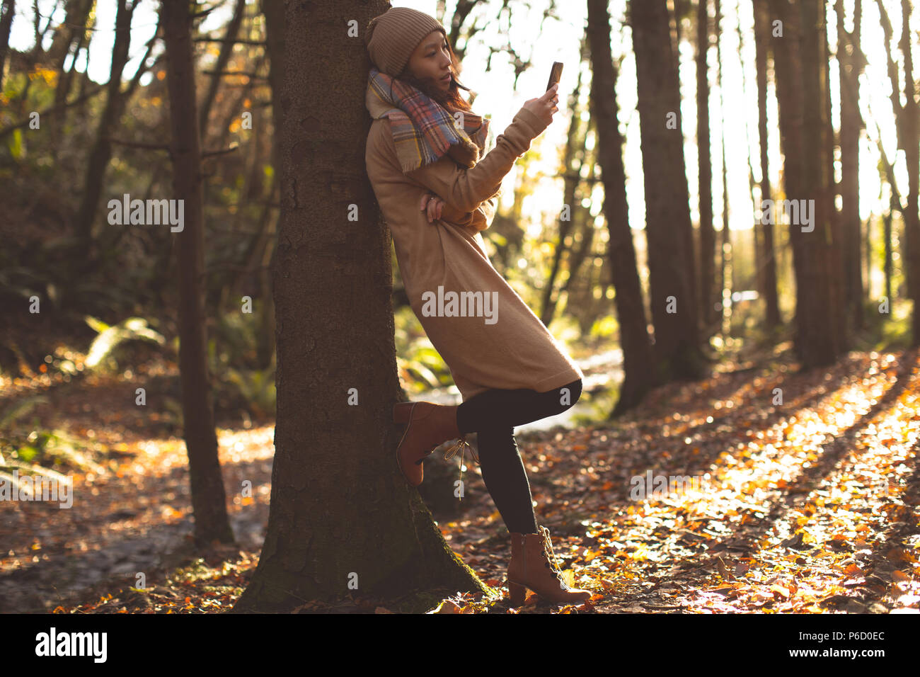 Bella donna di abbigliamento caldo utilizzando il telefono cellulare Foto Stock
