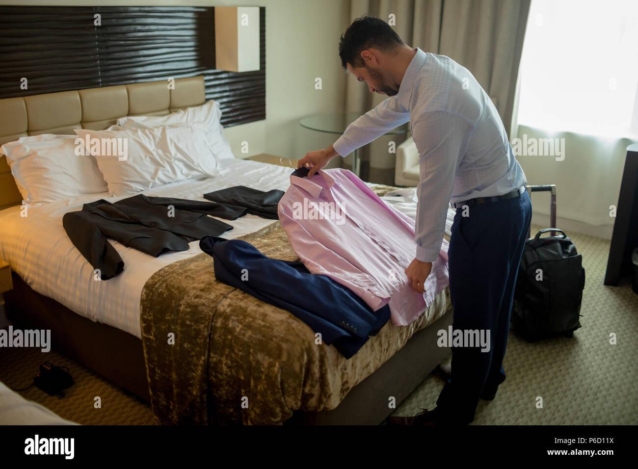 Imprenditore vestiti di imballaggio sul letto Foto Stock