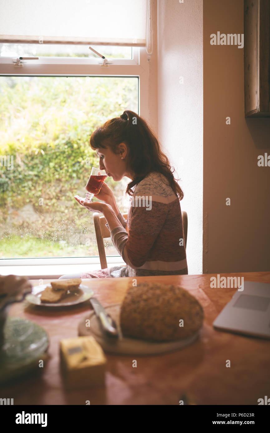 Donna con un tè a casa Foto Stock
