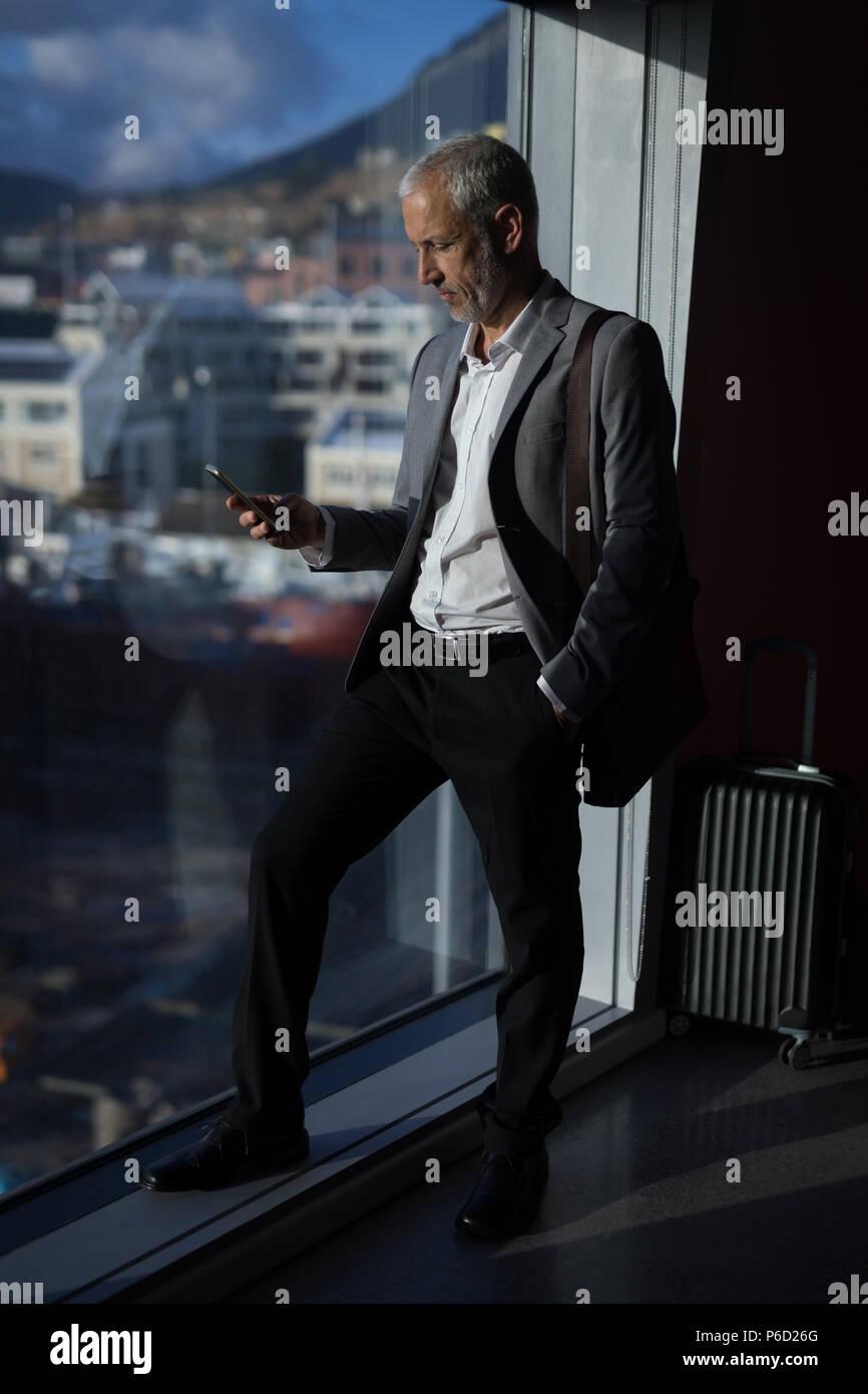 Imprenditore utilizzando il telefono cellulare nella camera di albergo Foto Stock