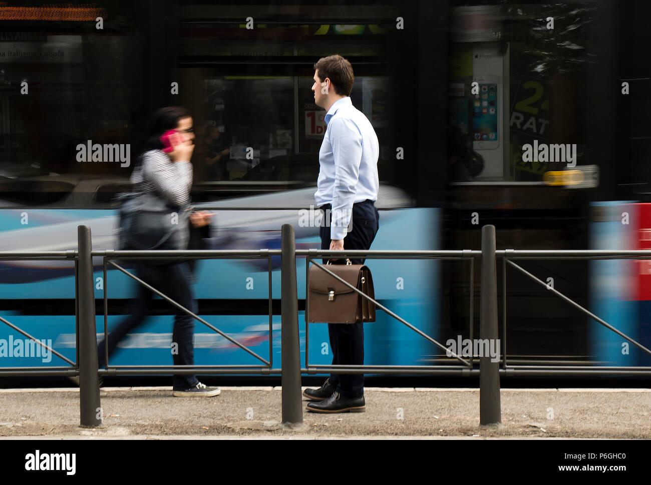 Belgrado, Serbia - Aprile 24, 2018 : uno bianco-collare Uomo con valigetta in piedi ad una fermata di autobus e di attesa per i mezzi di trasporto pubblici con motio sfocato Immagini Stock