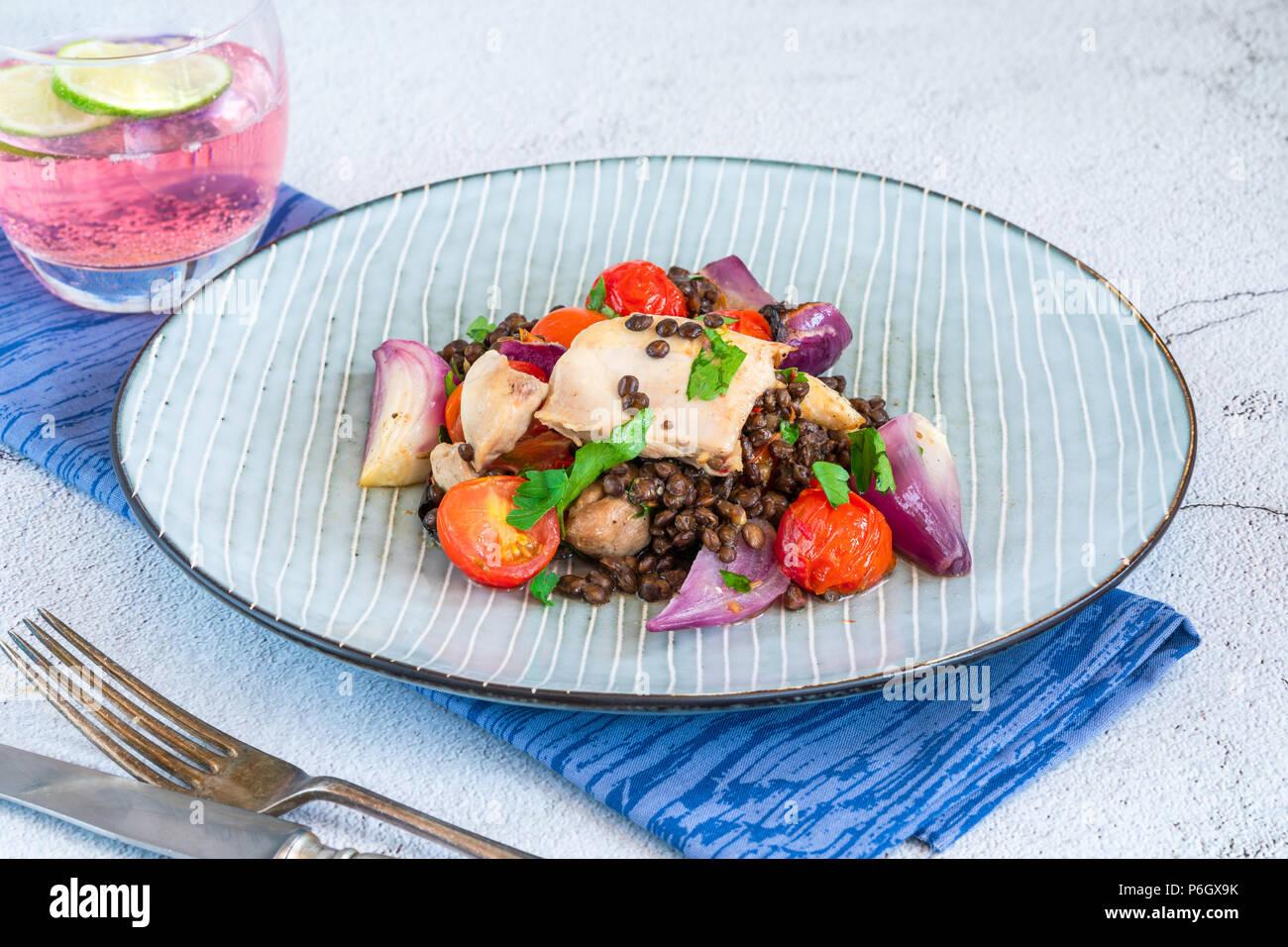 Pollo e pomodori ciliegia cuocere con le lenticchie di puy Immagini Stock