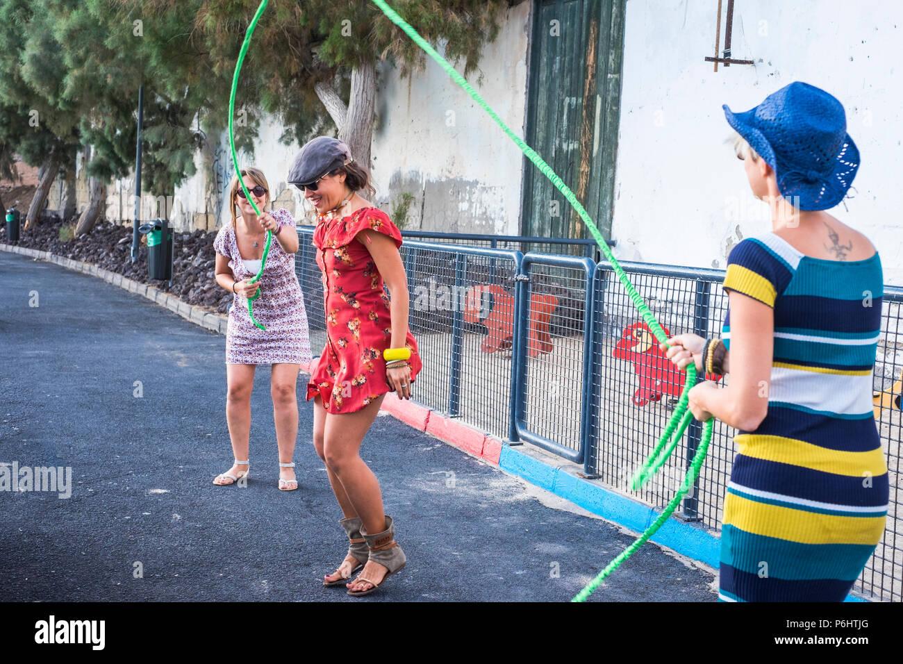 Il gruppo di donne persone divertendosi saltando una corda insieme come bambini. sensazione giovane e giocare all'aperto. Foto Stock