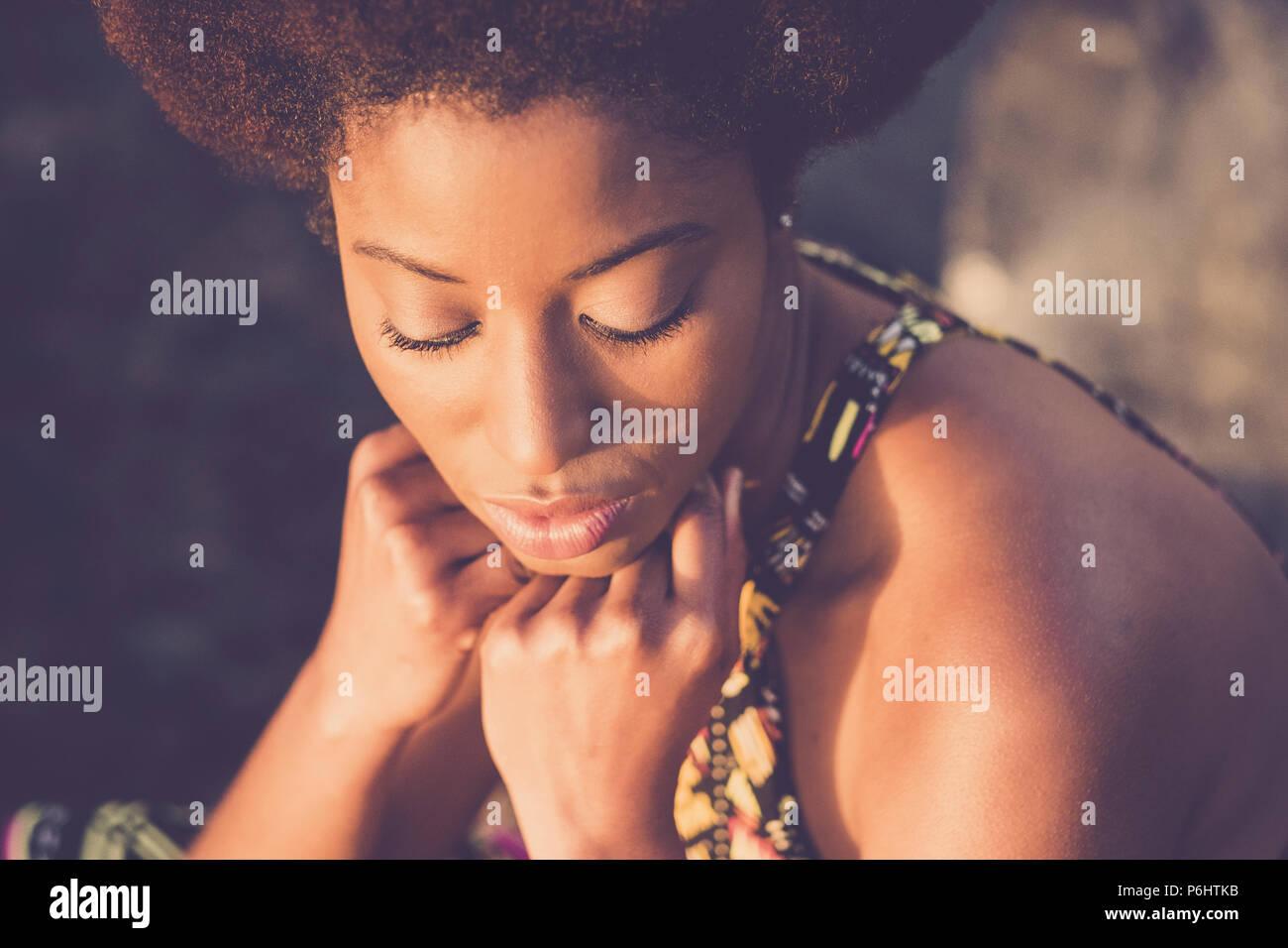 Bella gara nera africana di afro capelli stile modello con gli occhi chiusi e la mano sulla faccia pongono sotto la luce diretta del sole. Il concetto di bellezza per la pelle nera e a Immagini Stock