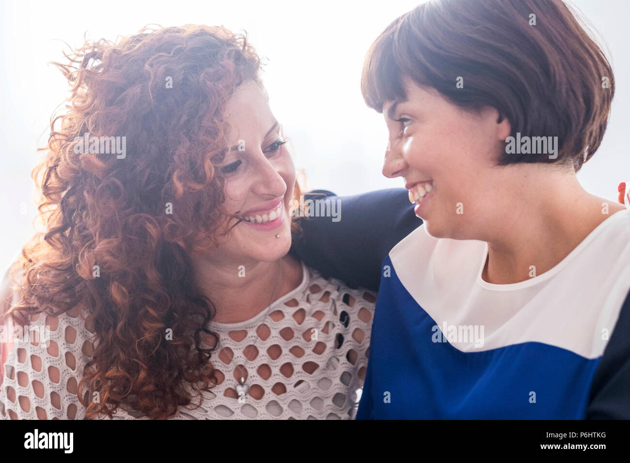 Coppia di amici di sesso femminile sorridente insieme ogni altra. Godetevi friendshiop e relazione. caucasian belle giovani donne con sfondo bianco Immagini Stock