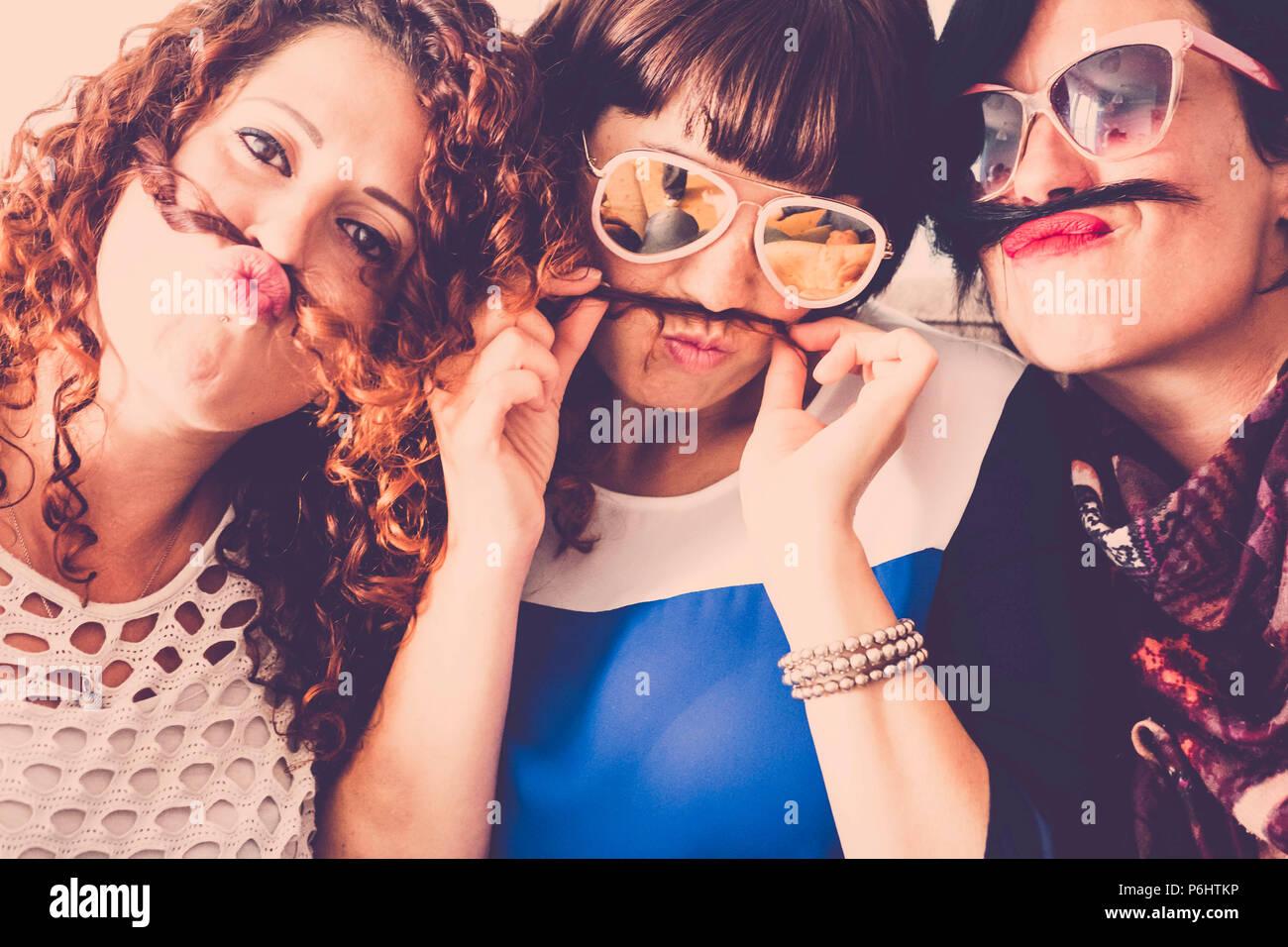 Tre femmine caucasica amici stare insieme in amicizia e follia usando i capelli come baffi e felicità il concetto di relazione. vintage c pieno Immagini Stock