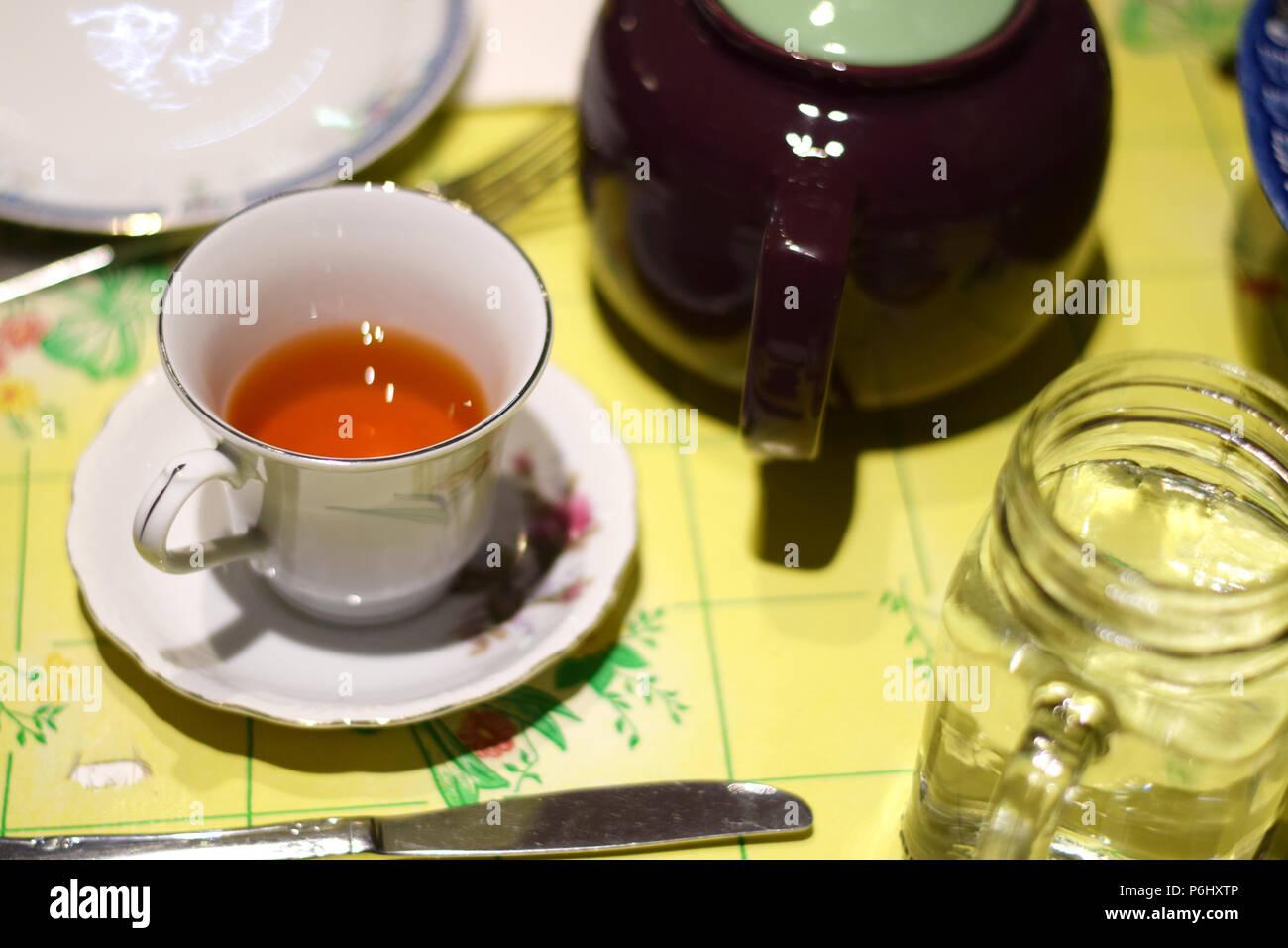 Tazza da tè sul tavolo con tè in esso Immagini Stock