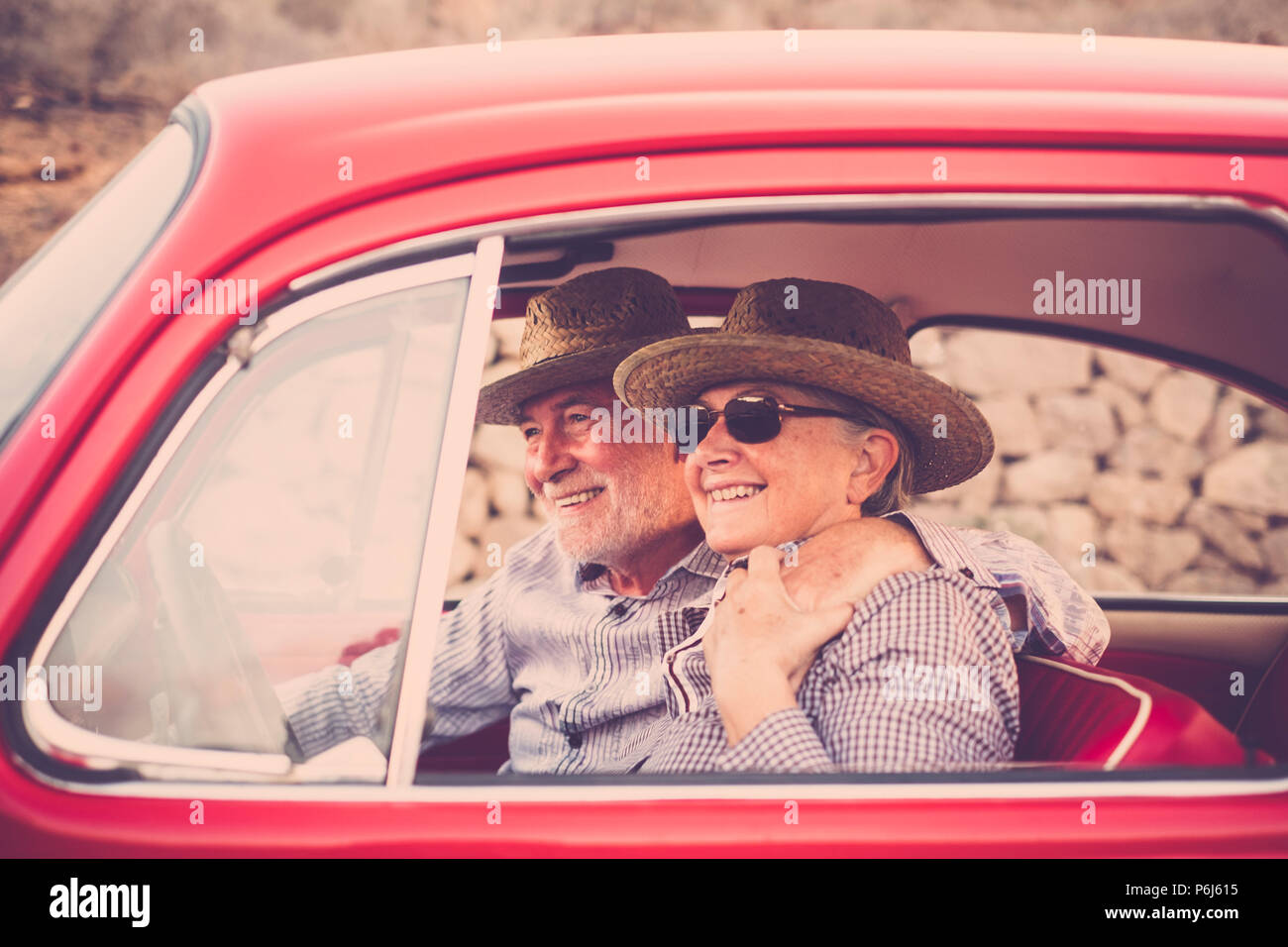 Coppia di anziani con cappello, con occhiali, con il grigio e il bianco dei capelli, con camicia casual, su vintage auto rossa in vacanza godendosi il tempo e la vita. Con un chee Immagini Stock