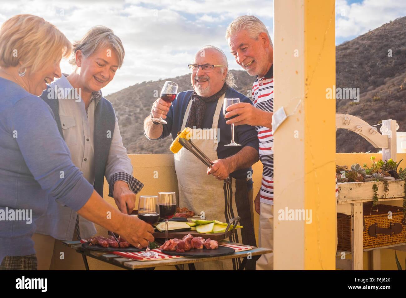 Quattro active senior pensionati hanno divertimento nella terrazza a casa la cottura di alcuni barbecue sorrisi a tutti e di stare insieme in amicizia sotto una bella giornata di sole. Immagini Stock