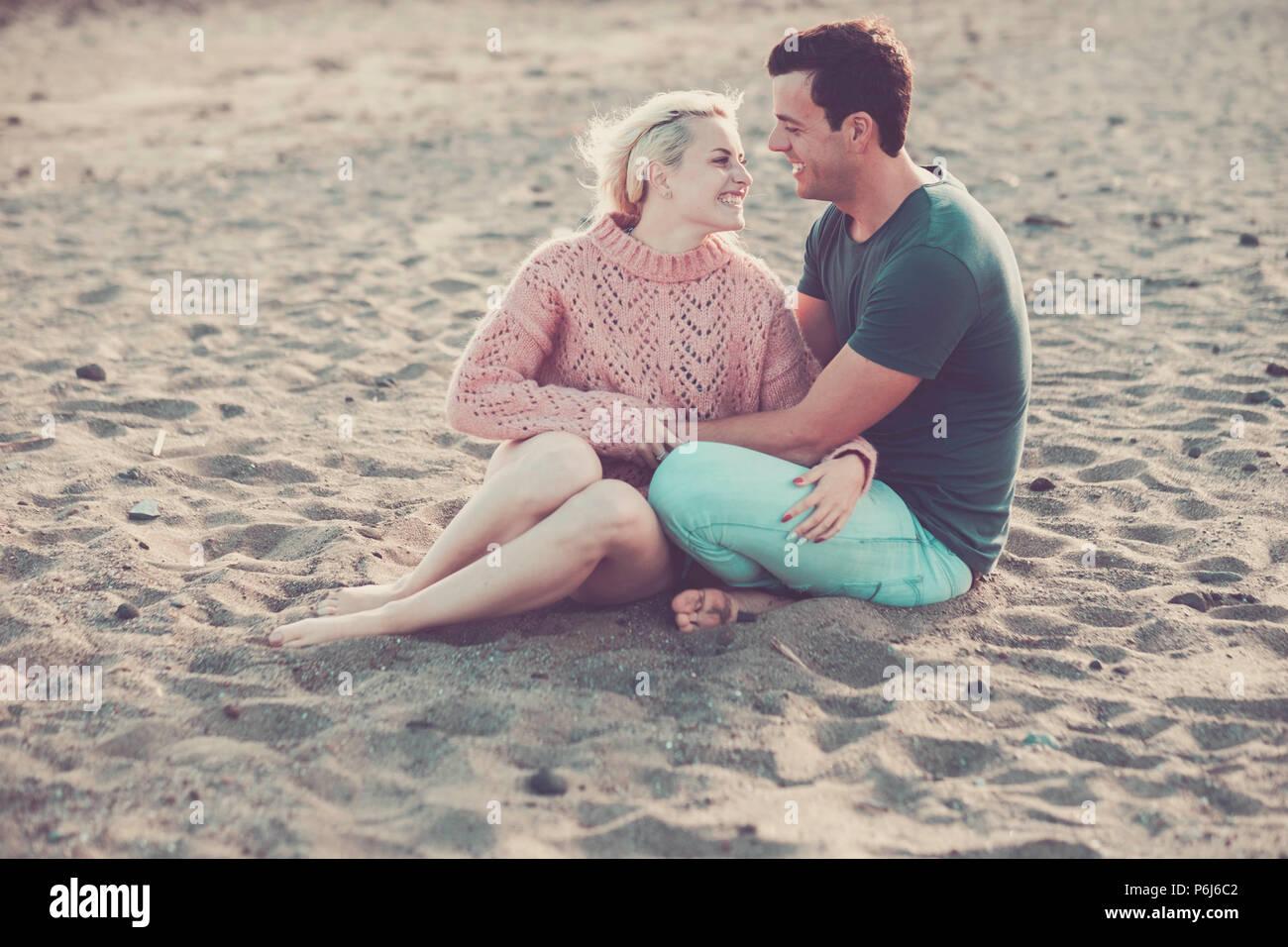 Bellissimo modello giovane caucasico giovane donna e uomo rimanere nell'amore abbracciando e seduto sulla spiaggia. bionda e capelli neri in rapporto all'aperto leisu Immagini Stock